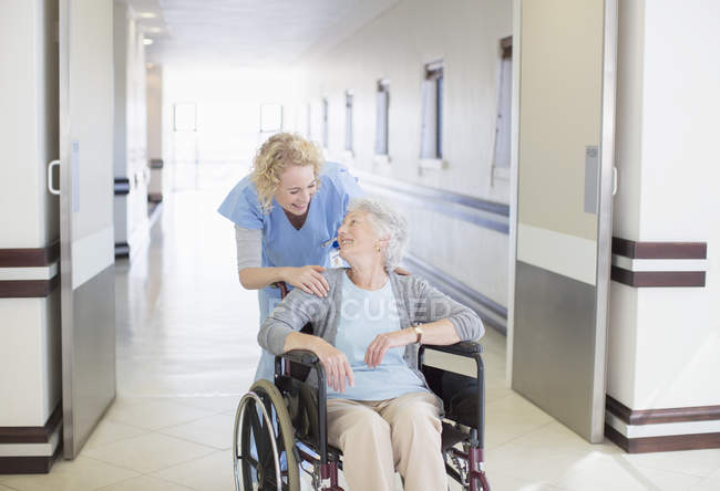 Nurse with aging patient in wheelchair in hospital corridor — Stock Photo