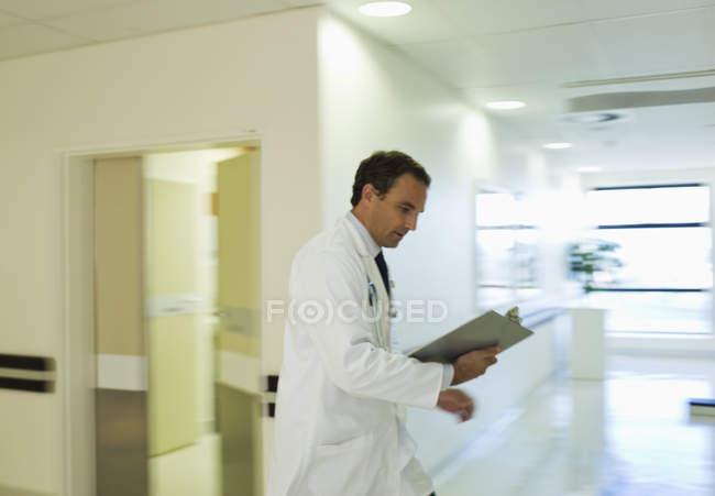 Доктор, чтением медицинской диаграммы в коридоре больницы — стоковое фото