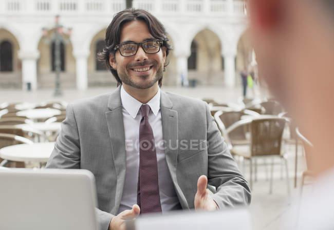 Uomo d'affari sorridente che parla con un collega al caffè sul marciapiede — Foto stock