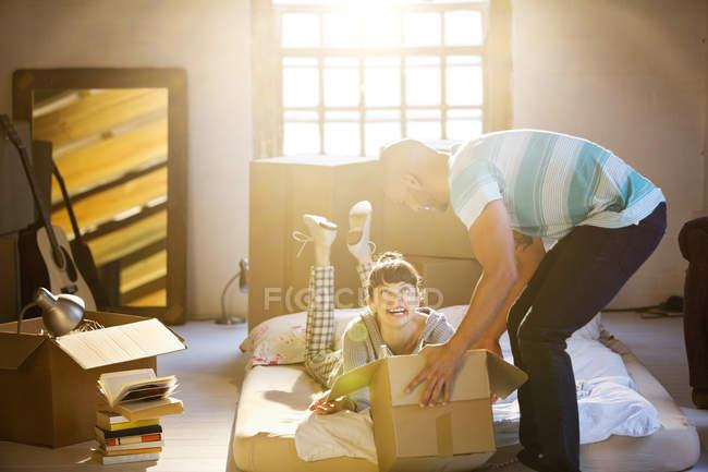Jeune couple déballage des boîtes dans le grenier — Photo de stock