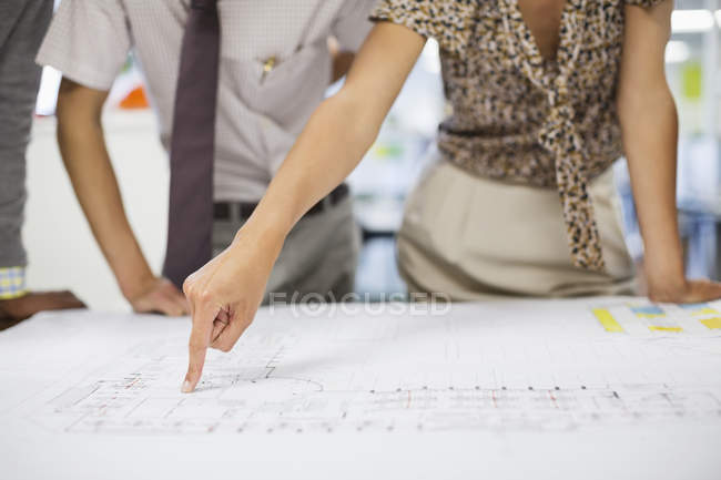 Cropped image of business people reading blueprints in meeting — Stock Photo