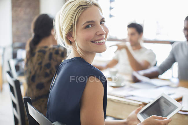 Businesswoman using digital tablet at meeting in cafe — Stock Photo