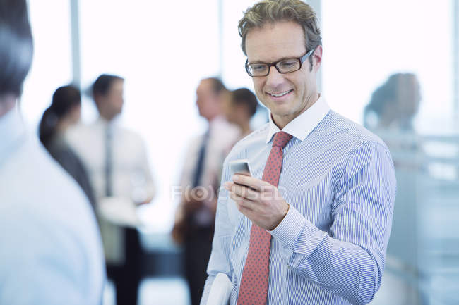 Businessman using cell phone at modern office — Stock Photo