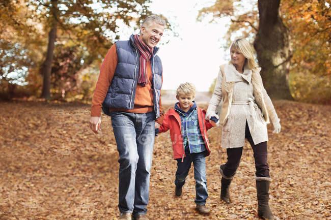 Älteres Paar spaziert mit Enkel in Park — Stockfoto