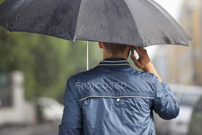 Homme parlant sur le téléphone portable sous le parapluie sous la pluie — Photo de stock