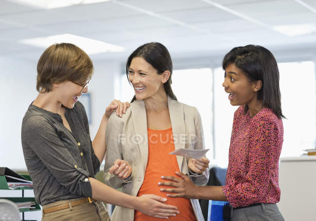 Colleagues admiring pregnant businesswoman?s belly — Stock Photo