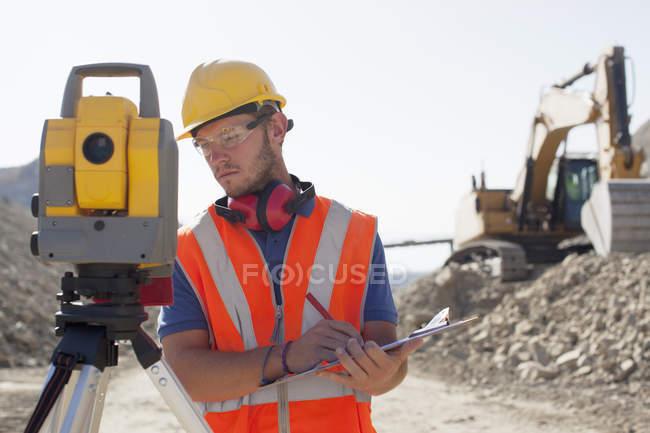 Работник с использованием выравнивания оборудования в карьер — стоковое фото
