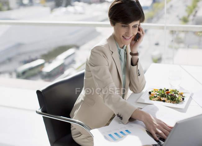 Businesswoman multitasking at desk — Stock Photo