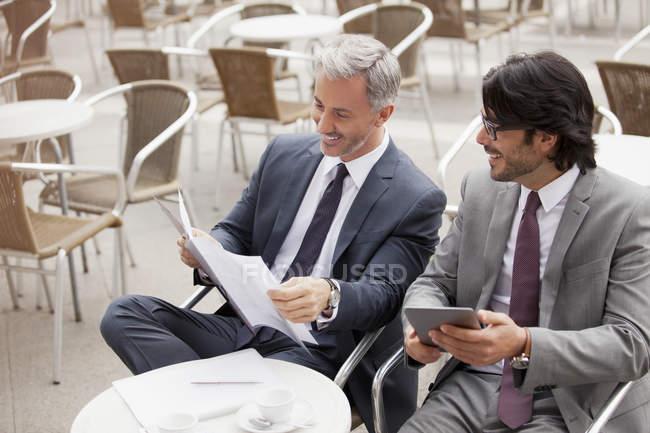 Усміхаючись бізнесменів з цифровий планшет і документи в кафе — стокове фото
