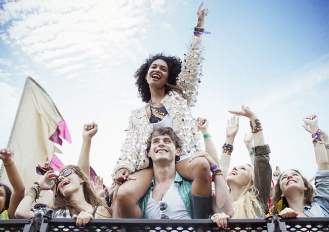 Cheering woman on man shoulders at music festival — Stock Photo