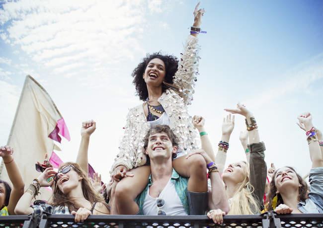 Femme encourageante sur les épaules de l'homme au festival de musique — Photo de stock