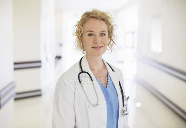 Portrait of smiling doctor in hospital corridor — Stock Photo