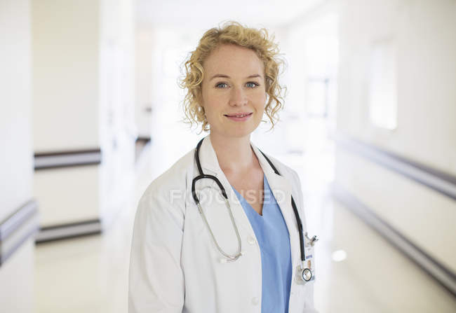 Portrait of smiling doctor in hospital corridor — Stock Photo