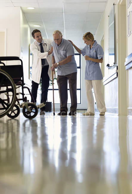 Doctor and nurse helping older patient walk in hospital — Stock Photo