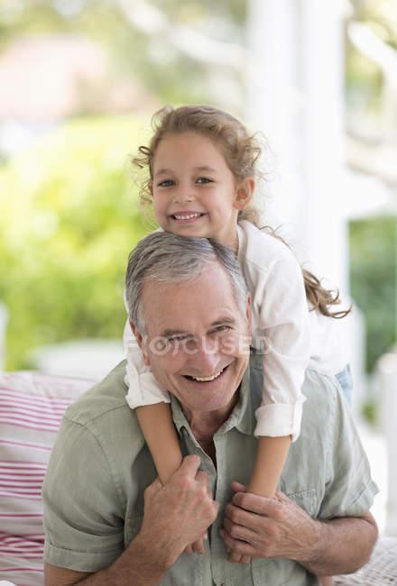 Взрослый мужчина с внучкой на спине — стоковое фото