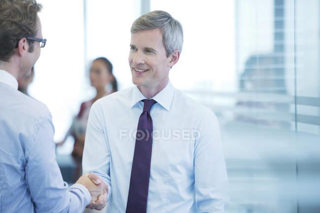 Бізнесмени, потискує руку на сучасні офісні — стокове фото