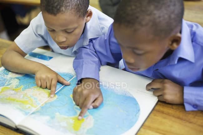 Étudiants afro-américains utilisant la carte du monde en classe — Photo de stock