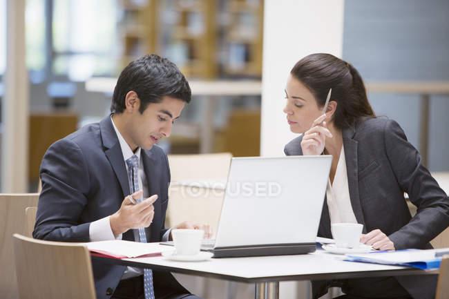 Empresário e empresária revendo a papelada no café — Fotografia de Stock