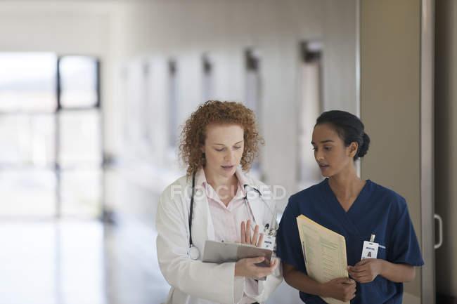 Médico e enfermeira conversando no corredor do hospital — Fotografia de Stock
