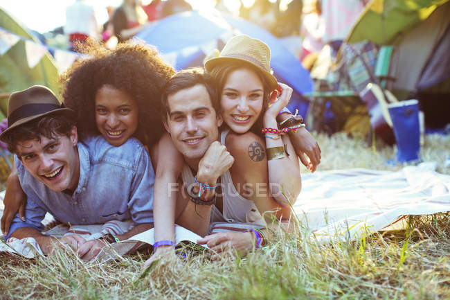 Portrait of friends laying on blanket outside tents at music festival — Stock Photo