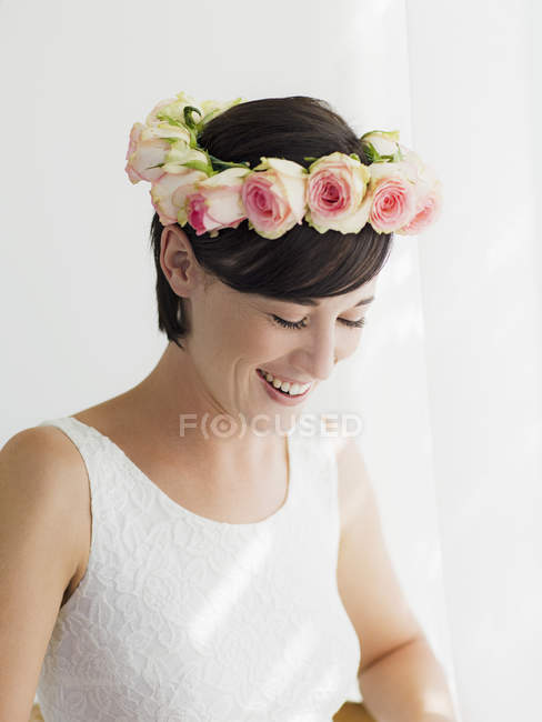 Smiling bride wearing rose wreath on head — Stock Photo