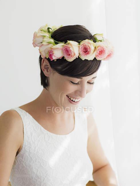 Novia sonriente con corona de rosas en la cabeza - foto de stock