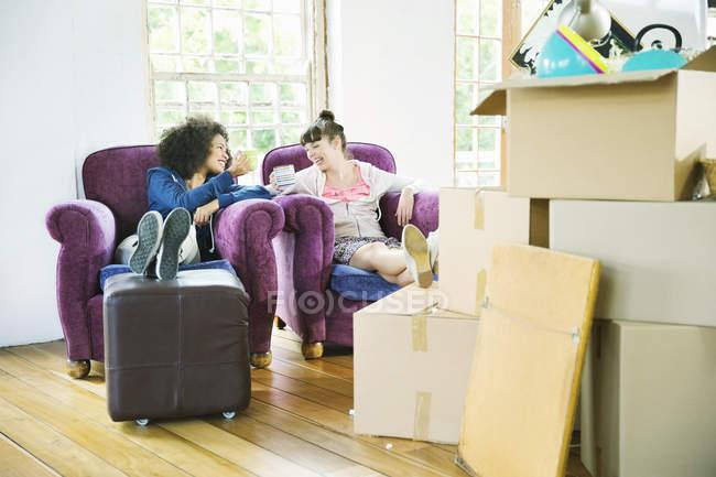 Jeunes femmes heureuses prenant un café ensemble dans une nouvelle maison — Photo de stock