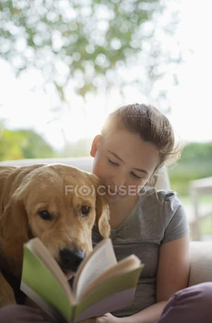 Дівчина читання з собакою у крісло в сучасному будинку — стокове фото