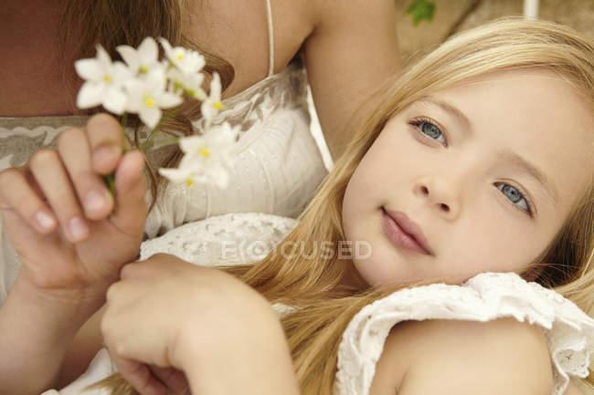 Close up of serene girl holding flower — Stock Photo