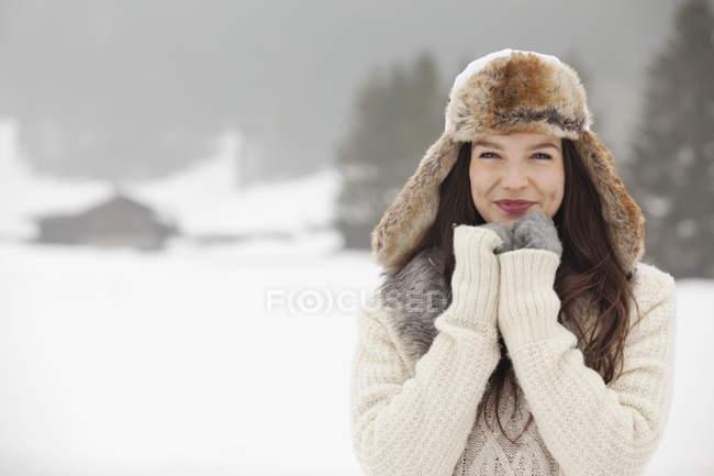 Портрет усміхається жінка, носіння хутра Шапочку та рукавички у snowy сфера — стокове фото