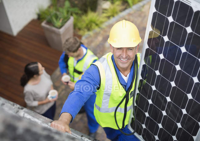 Worker installing solar panel on roof — Stock Photo