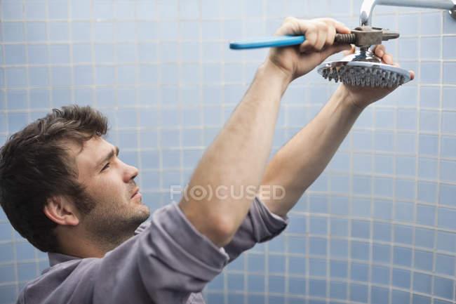 Skillful caucasian plumber working on shower head in bathroom — Stock Photo