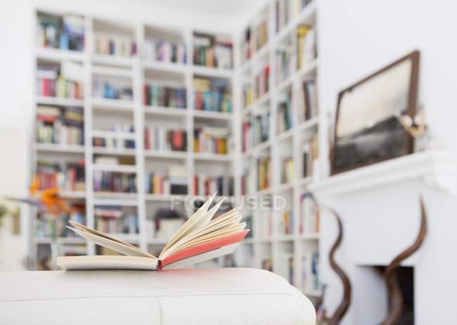 Открытая книга на руке дивана в гостиной — стоковое фото