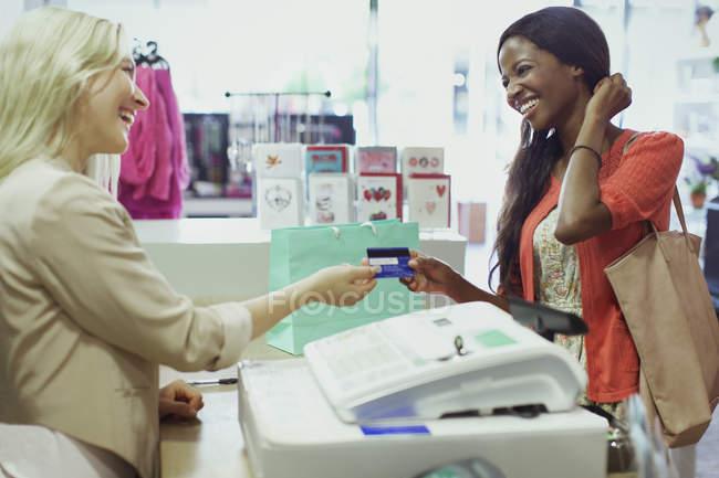 Donna che paga con carta di credito in negozio — Foto stock