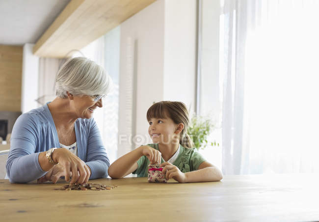 Older woman and granddaughter filling change jar — Stock Photo