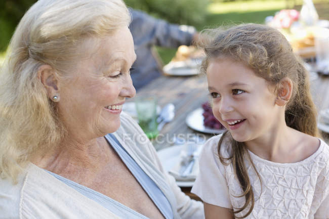 Пожилая женщина сидит с внучкой на улице — стоковое фото