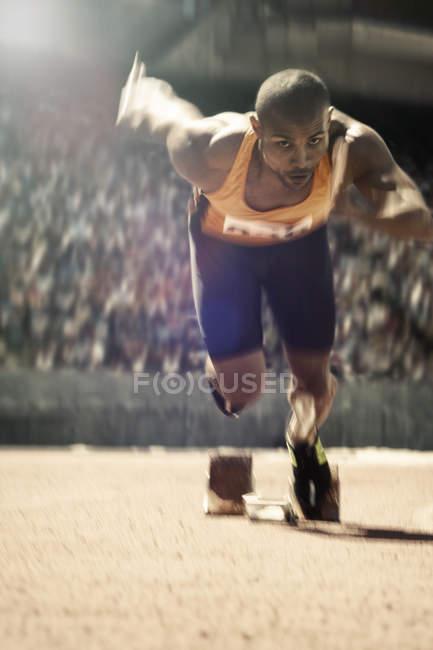 Бігун, знімаючи з стартову блок на треку — стокове фото