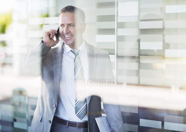 Homme d'affaires parlant sur téléphone portable au bureau moderne — Photo de stock