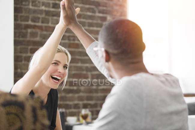 Business people high fiving at meeting in cafe — Stock Photo