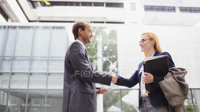 Ділові люди вітають один одного за межами Офісна будівля — стокове фото