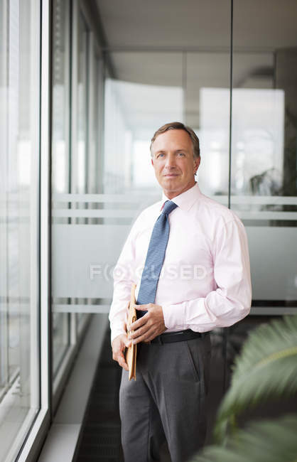 Businessman standing at modern office window — Stock Photo