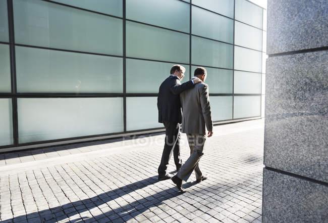 Rear view of businessmen talking on city street — Stock Photo