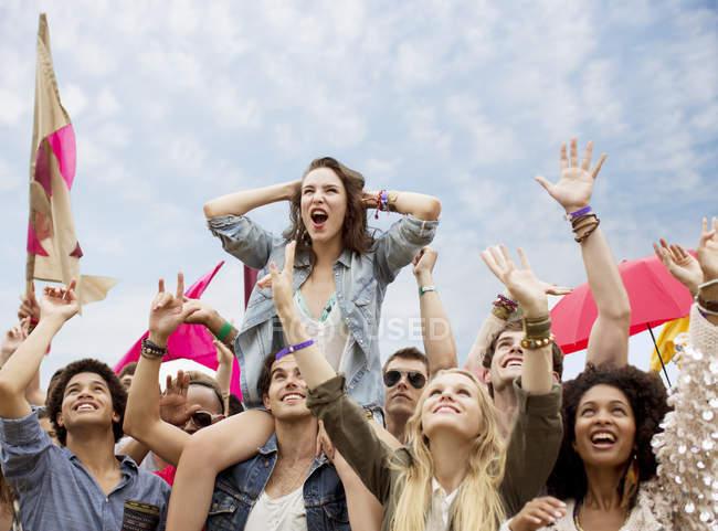 Аплодирующие женщины на мужских плечах на музыкальном фестивале — стоковое фото
