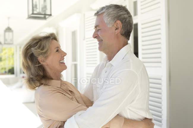 Senior kaukasischen Paar umarmen sich auf der Terrasse — Stockfoto