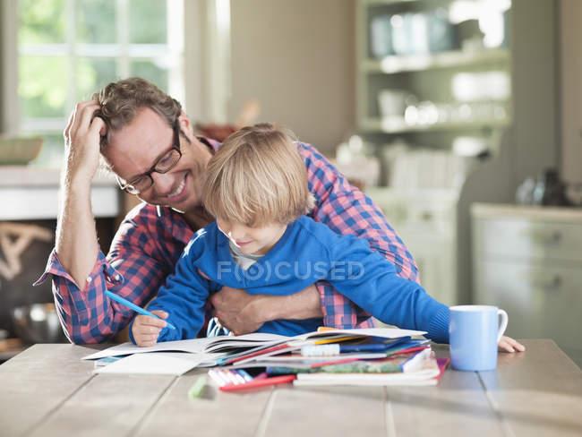 Отец и сын делают домашнее задание за кухонным столом — стоковое фото