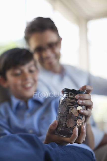Father and son holding change jar — Stock Photo