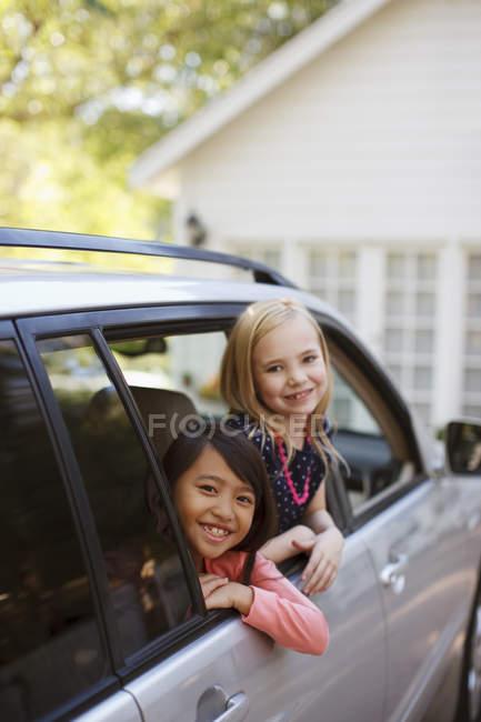 Niñas sonriendo hacia fuera la ventana de coche - foto de stock
