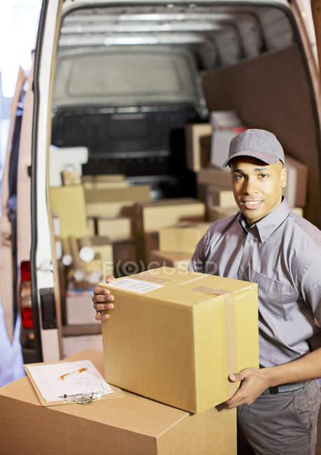Курьер загружает коробки в фургон. — стоковое фото
