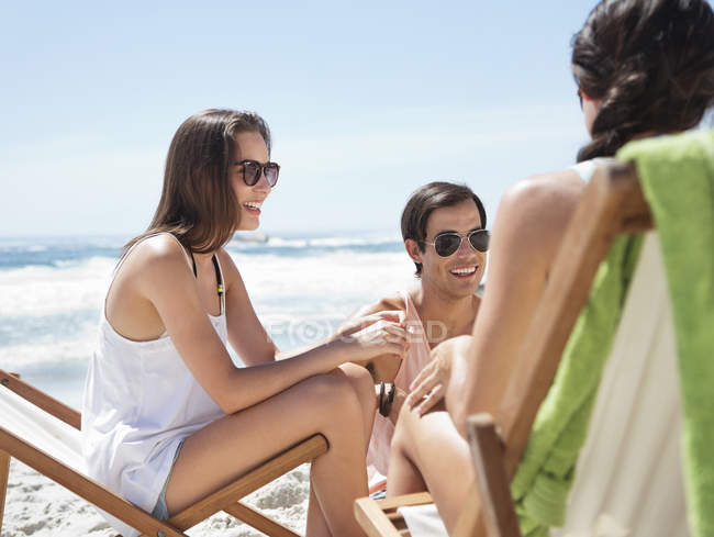 Happy caucasian friends hanging out at beach — Stock Photo