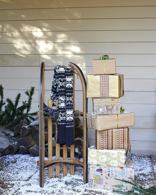 Sciarpa, slitta di legno e regali di Natale sul portico innevato — Foto stock